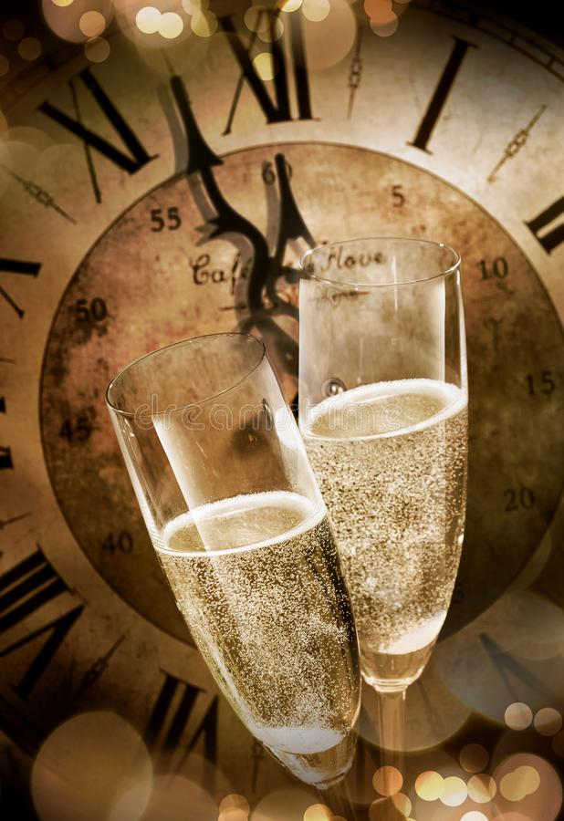 Two champagne flutes toasting before midnight stock images