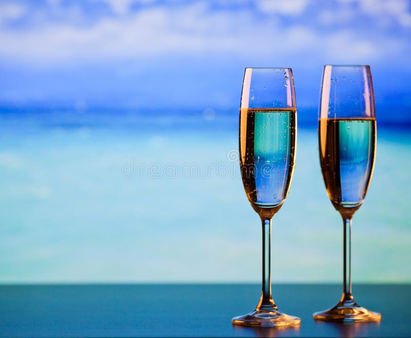 Two champagne glasses on the beach - exotic New Year stock image