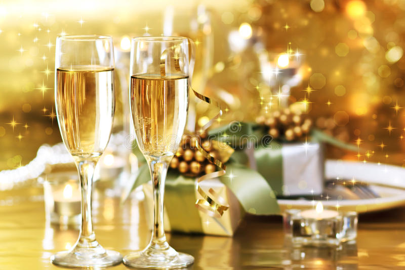 Two champagne glasses on the dinner table. With gift boxes