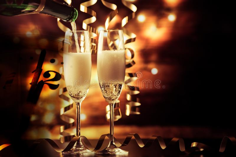 two champagne glasses with ribbons against holiday lights and fireworks - New Year celebrations royalty free stock photography