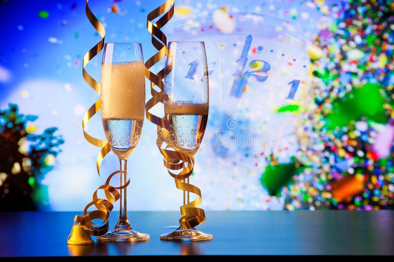 two champagne glasses with ribbons and falling confetti - New Year celebrations royalty free stock photo