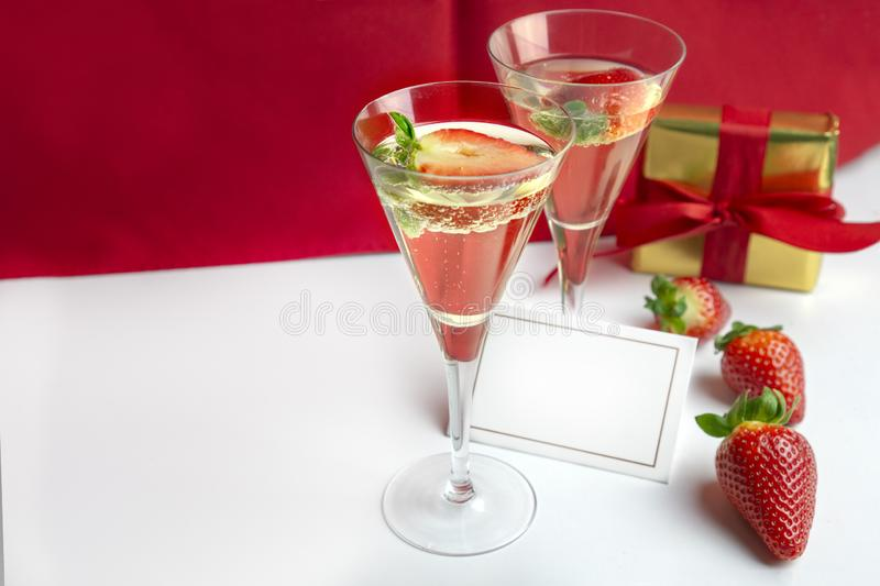 Two champagne glasses with strawberries and an empty card between them with a gift in the background . Valentine`s Day stock photo