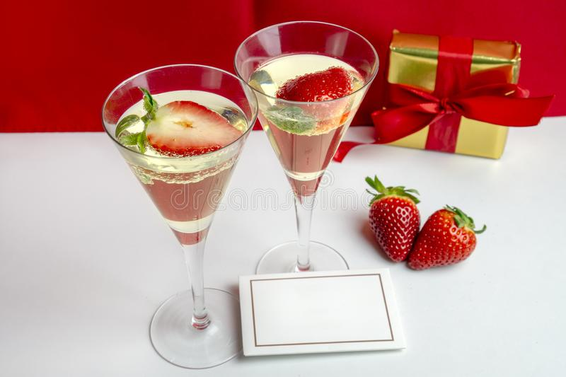 Two champagne glasses with strawberries and an empty card between them with a gift in the background . Valentine`s Day royalty free stock image