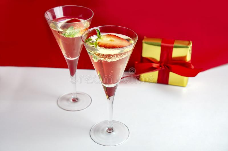 Two champagne glasses with strawberries and a gift in the background Valentine`s Day concept stock photos