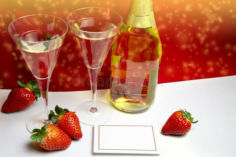 Two champagne glasses with strawberries and light shower copy space. Valentine`s Day concept royalty free stock photo
