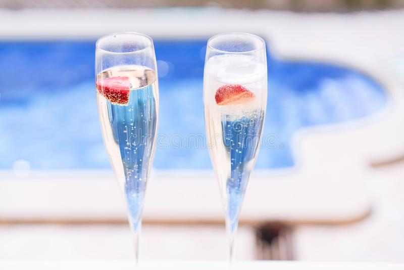 Two champagne glasses with strawberry on sunny terrace outdoor patio overlooking swimming pool at summer day outside of royalty free stock images