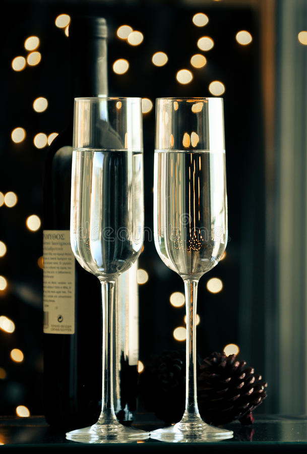 Two champagner glasses on glass table with black bokeh background. Two champagner glasses on glass table with black background royalty free stock image