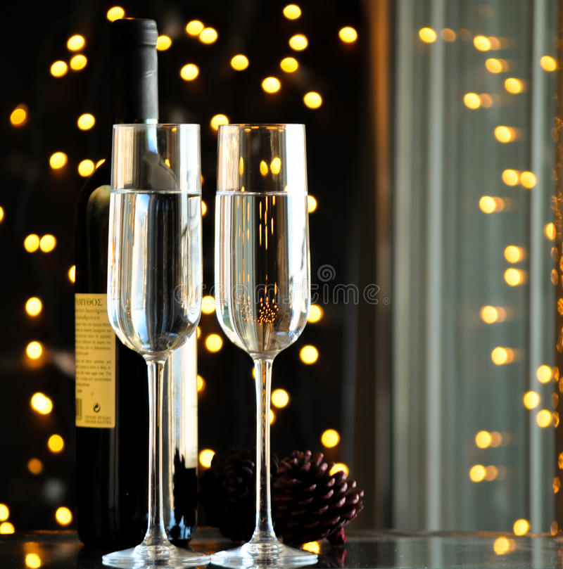 Two champagner glasses on glass table with black bokeh background. Two champagner glasses on glass table with black background stock photography