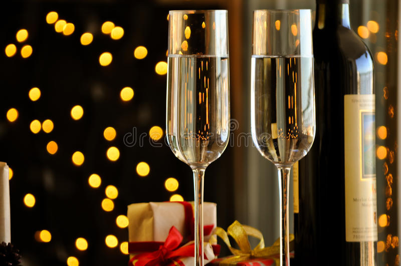 Two champagner glasses on glass table with black bokeh background. Two champagner glasses on glass table with black background stock images