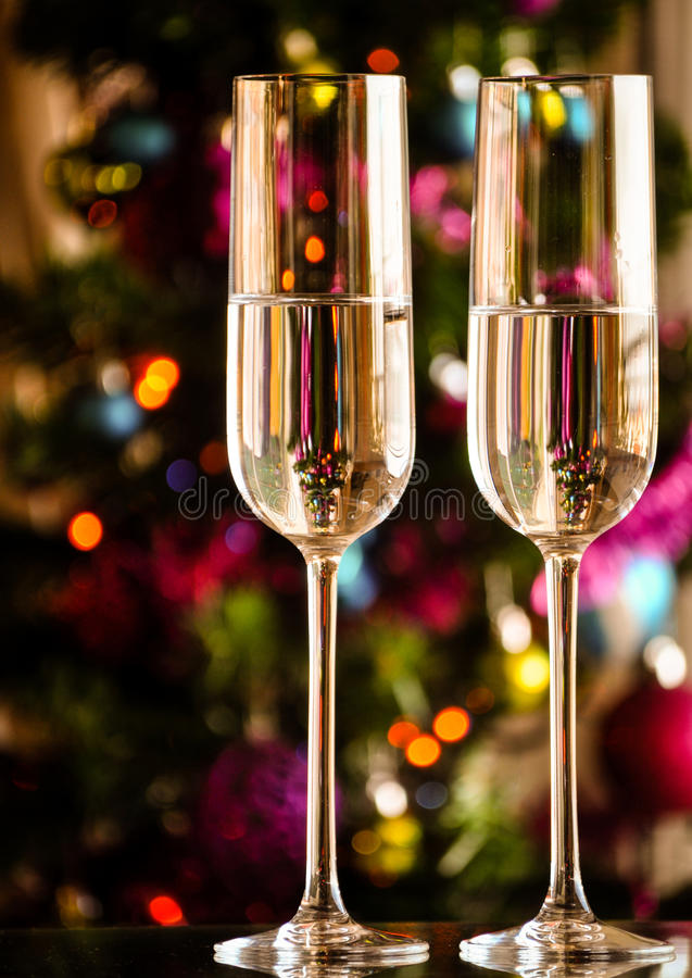 Two champagner glasses on glass table with bokeh background with place for text. Two champagner glasses on glass table with bokeh background and lights stock image