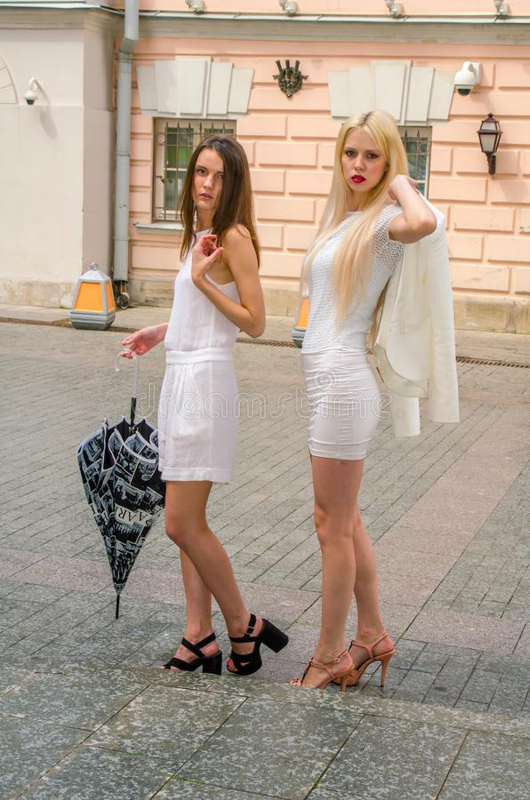 Two friends blonde and brunette in white dresses hiding from the weather under a large umbrella in the alleys of the old city royalty free stock photography