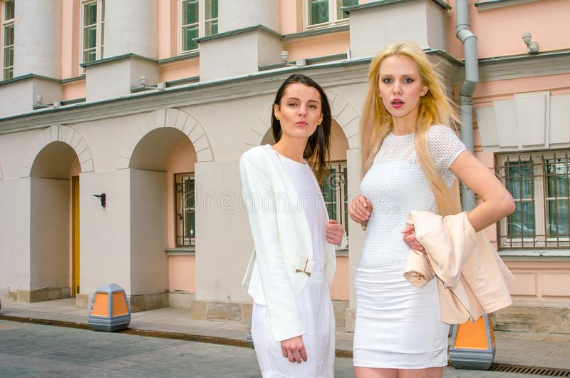 Two friends blonde and brunette in white dresses posing on the street of the old city stock image
