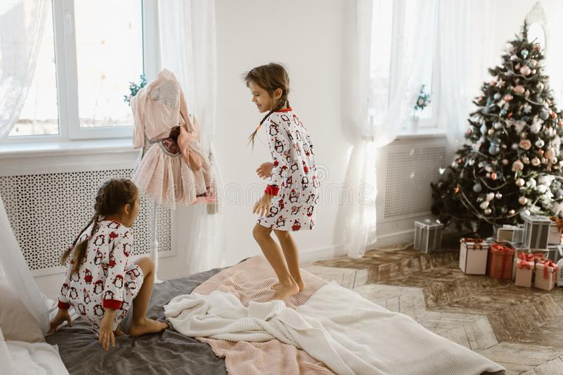 Two charming little girls in their pajamas are having fun jumping on a bed in a sunlit cozy bedroom with New Year`s tree stock images