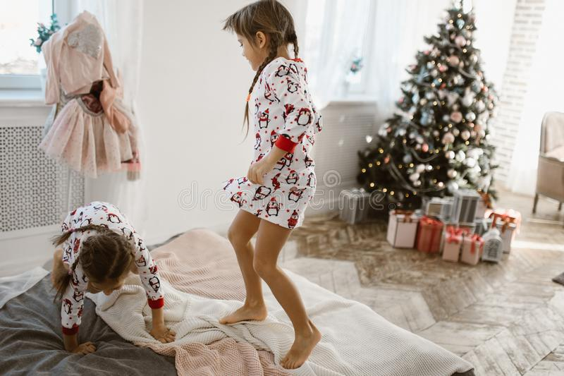 Two charming little girls in their pajamas are having fun jumping on a bed in a sunlit cozy bedroom with New Year`s tree stock photos