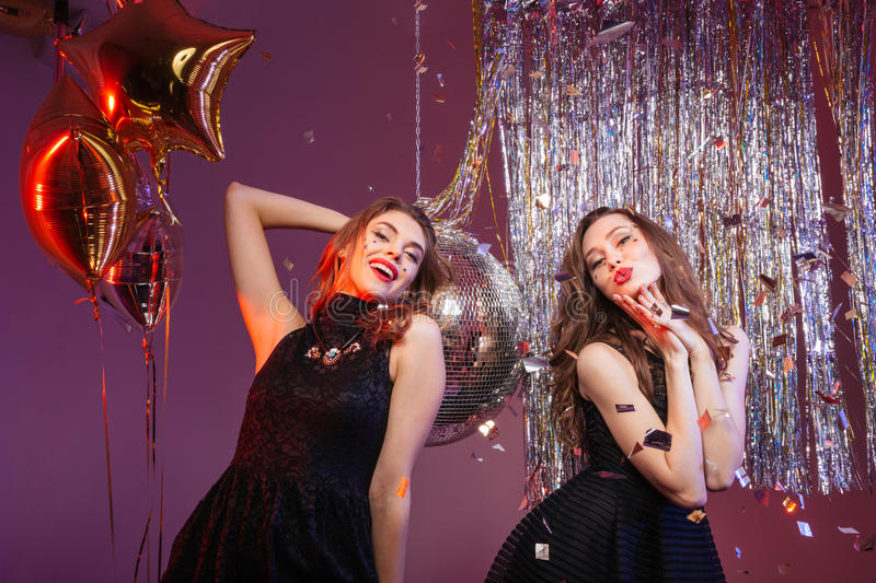 Two charming playful women dancing and having party. Two charming playful young women in black dresses dancing and having party over purple background stock images