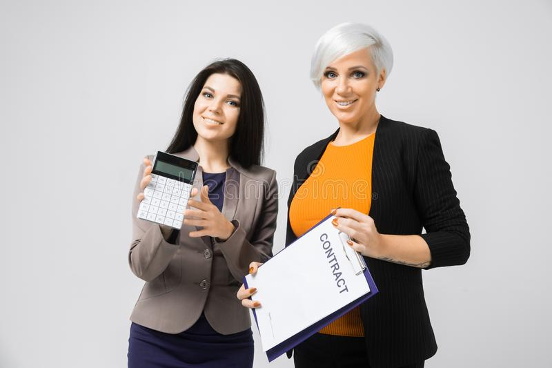 Portrait of two young girls with calculator and contract in hands isolated on light background stock images