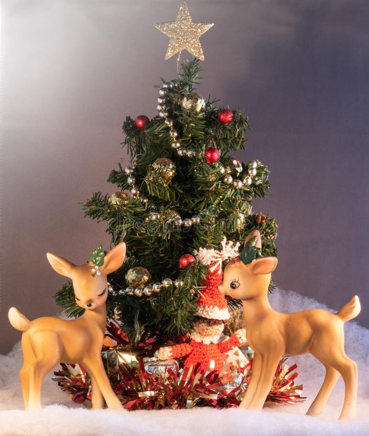 Two charming vintage figurines of romantic little flirting reindeer in front of a miniature decorated Christmas tree with gifts. And a gold star on top royalty free stock photography