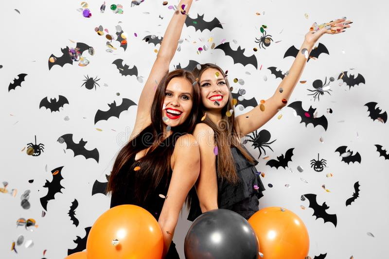 Two charming women in witches hats have fun with confetti and hold black and orange balloons on a white background with. Black bats and spiders stock photos