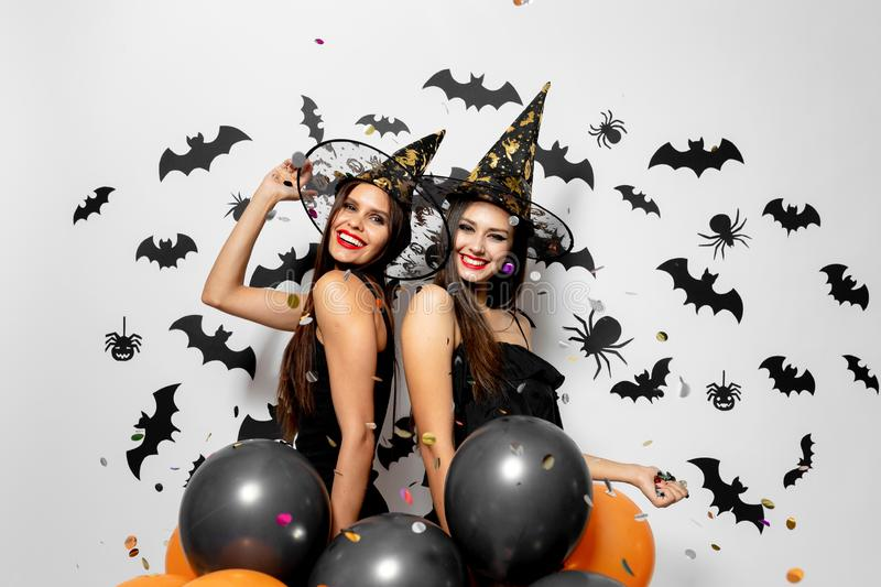 Two charming women in witches hats have fun with confetti and hold black and orange balloons on a white background with. Black bats and spiders stock image
