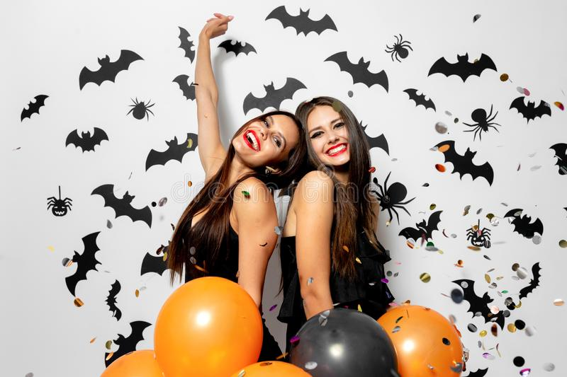Two charming women in witches hats have fun with confetti and hold black and orange balloons on a white background with. Black bats and spiders royalty free stock photos