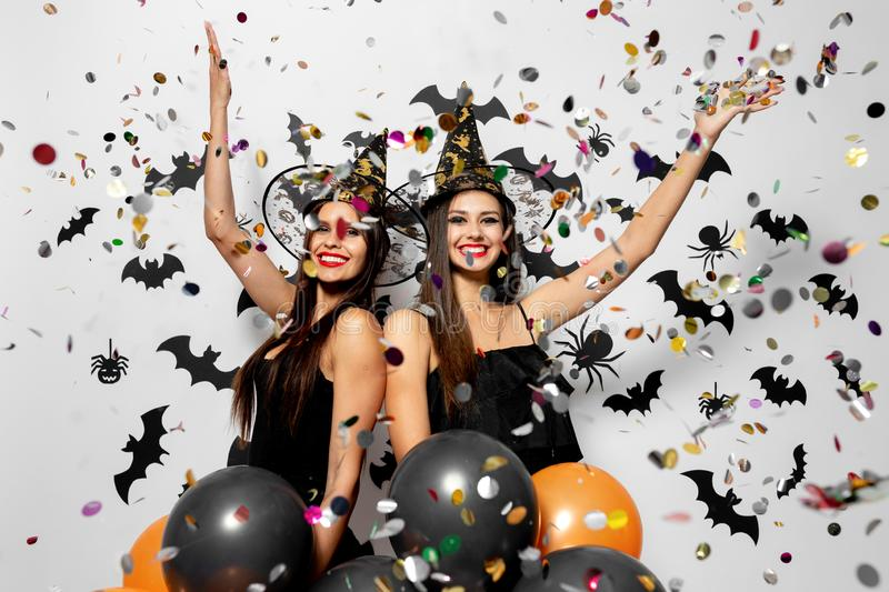 Two charming women in witches hats have fun with confetti and hold black and orange balloons on a white background with. Black bats and spiders royalty free stock photo