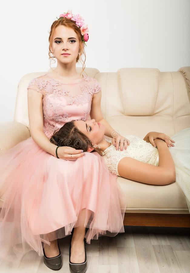 Two charming young women in elegant dresses sitting on a sofa, tender history stock image