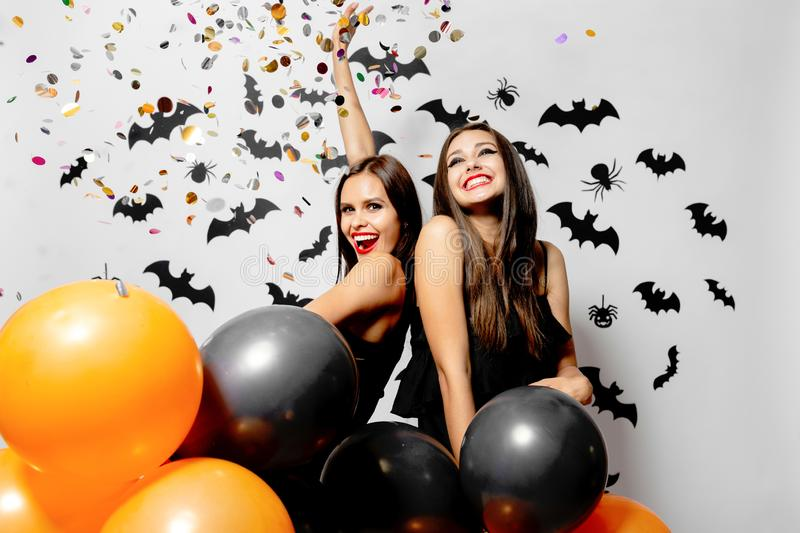 Two charming young women in witches hats smile, have fun with confetti and hold black and orange balloons. Halloween. Mood stock images