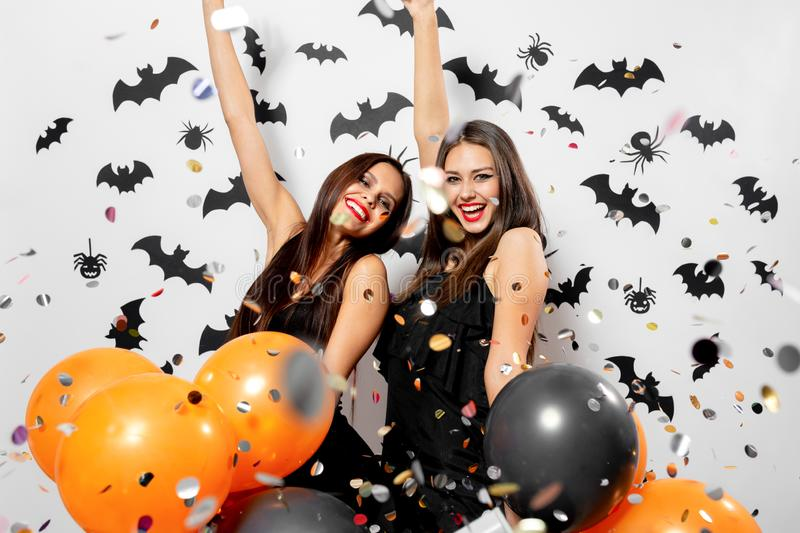 Two charming young women in witches hats smile, have fun with confetti and hold black and orange balloons. Halloween. Mood royalty free stock image