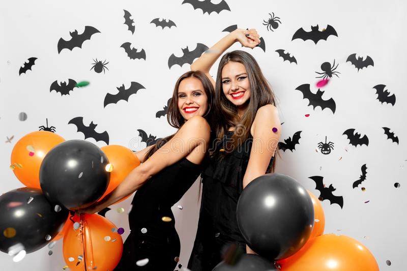 Two charming young women in witches hats smile, have fun with confetti and hold black and orange balloons. Halloween. Mood stock photo