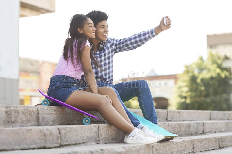 Two cheerful african teenagers taking selfie outdoors royalty free stock photo