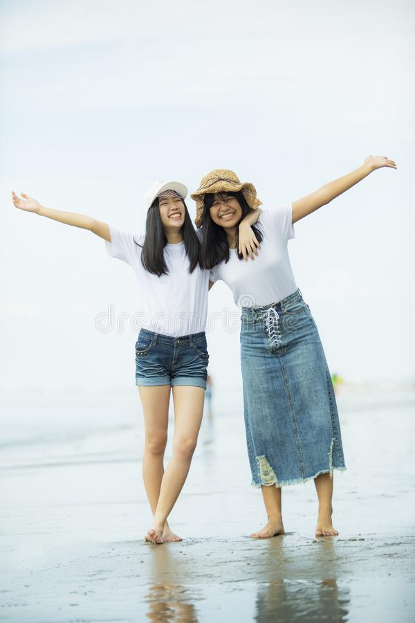 Two cheerful asian teenager happiness on vacation sea beach royalty free stock photos