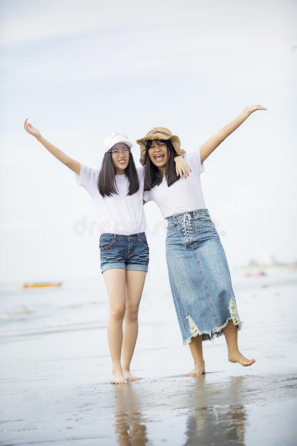 Two cheerful asian teenager happiness on vacation sea beach stock image