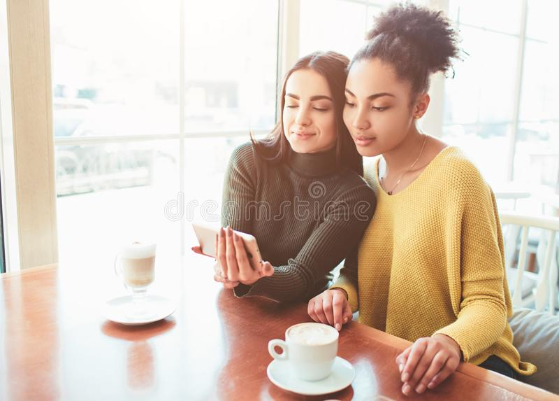 Two cheerful and beautiful girls are sitting together near the table and watching something on the phone. They look. Relaxed and happy. Also girls are enjoying stock images