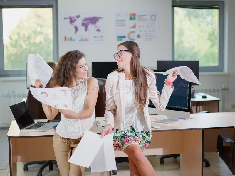 Two cheerful beautiful young business girls in the office. royalty free stock photo
