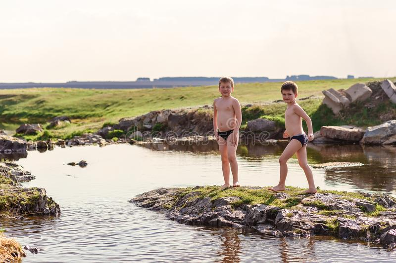 Two cheerful boys in bathing shorts play on a small river in the village. In the summer royalty free stock photos