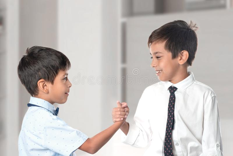 Two cheerful boys wearing shirts and ties shake each other hands as a token of friendship stock photography