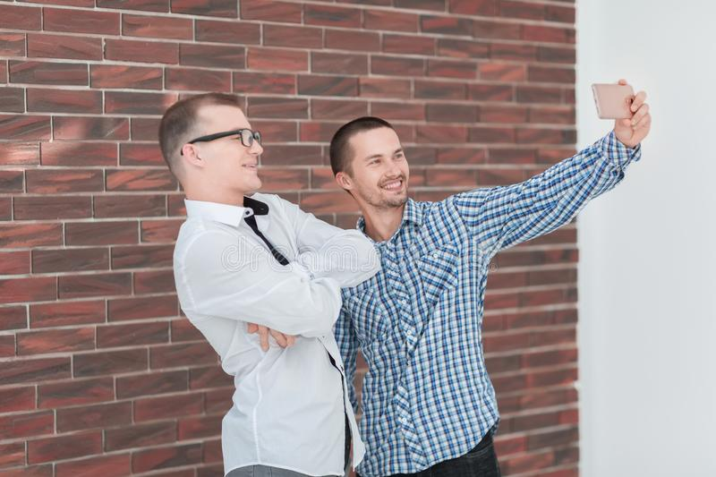 Two cheerful co-workers taking selfies standing in the office. People and technology stock image