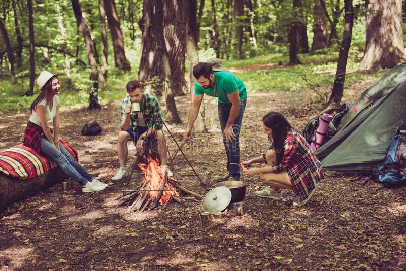 Two cheerful couples of young hikers are getting ready for a meal, lady cooks, guy is fixing the fire, other couple chilling, sit. Ting, nice camp, summer sunny stock images