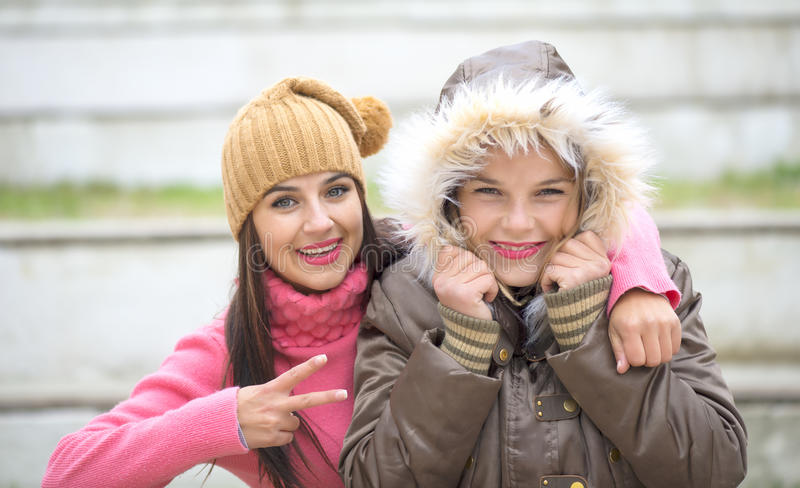 Two cheerful cute girls, one hugging her best female friend outdoors. In winter stock images