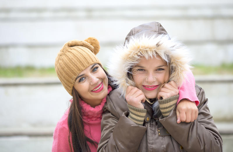 Two cheerful cute girls, one hugging her best female friend outdoors. In winter stock image
