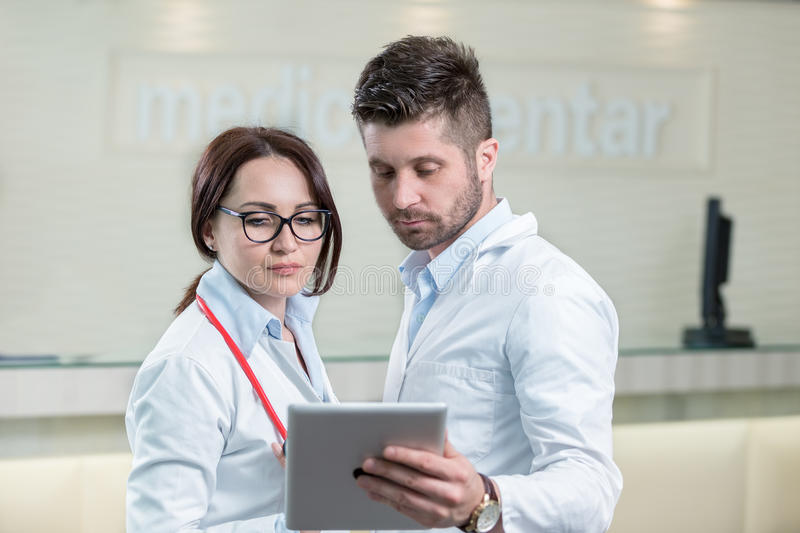 Two cheerful doctors using a digital tablet. royalty free stock images
