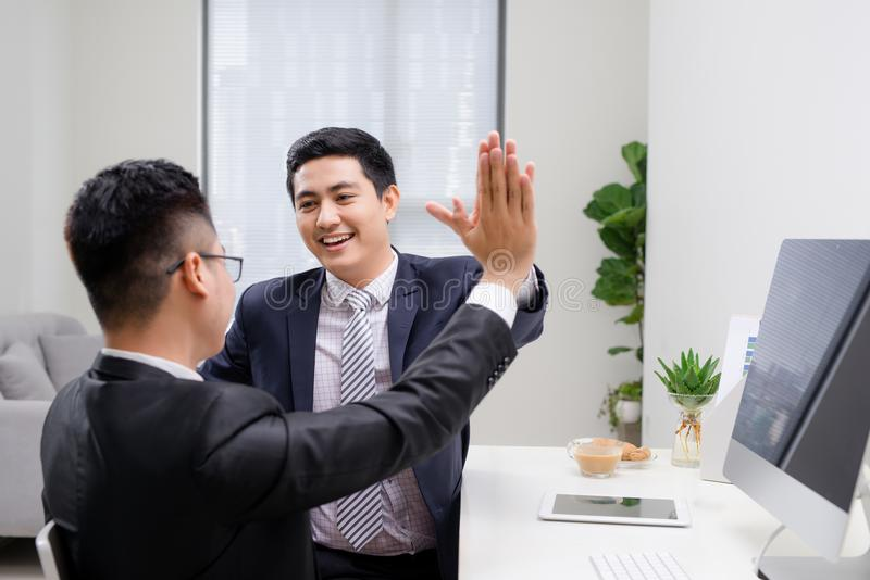 Two cheerful excited young men giving high five and working in office together. Two cheerful excited young men giving high five and working in office together stock photos