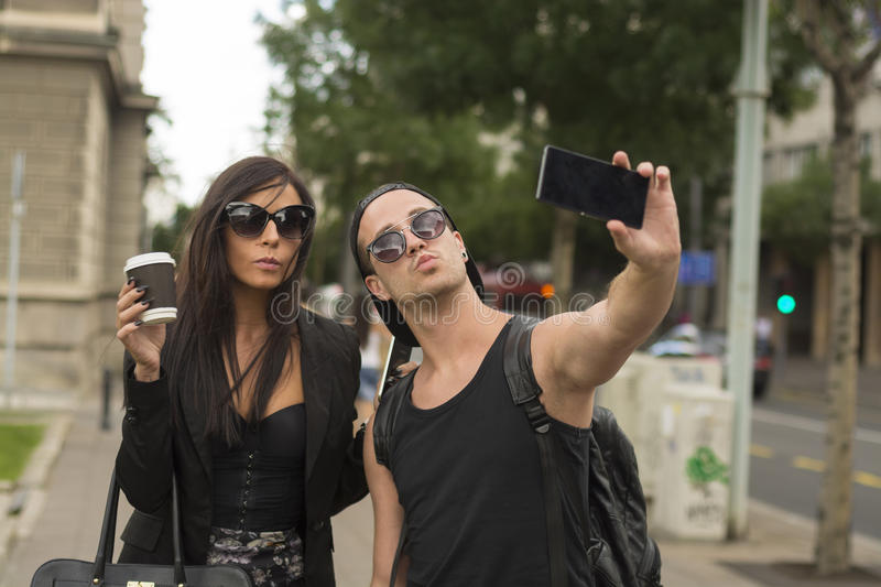 Two cheerful friends taking photos of themselves on smart phone royalty free stock photography