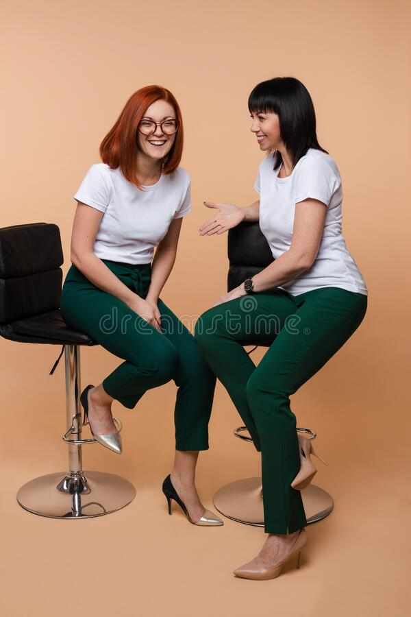 Two cheerful girl friend laughing gossiping sitting chair isolated at studio background stock image
