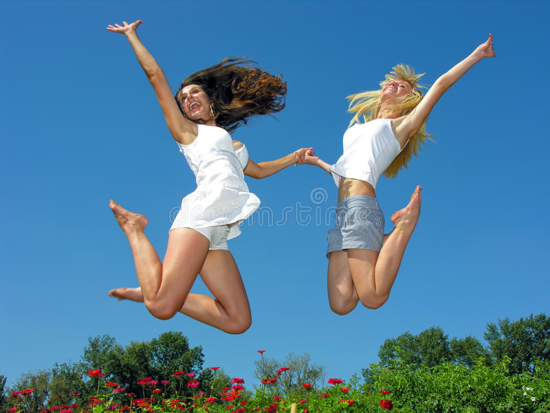 Two cheerful girlfriends jumping outdoors stock image