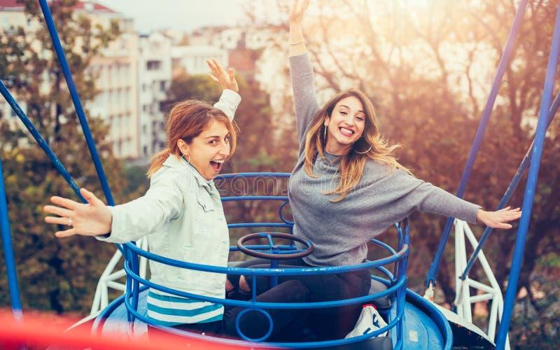 Two cheerful girls having fun on merry go round stock photo