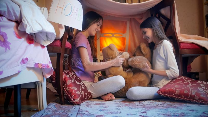 Two cheerful girls playing with teddy bears in bedroom at night. Two girls playing with teddy bears in bedroom at night stock photography