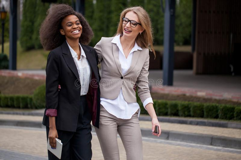 Two cheerful pretty african and caucasian businesswomen in stylish suits are walking along the park. royalty free stock photos