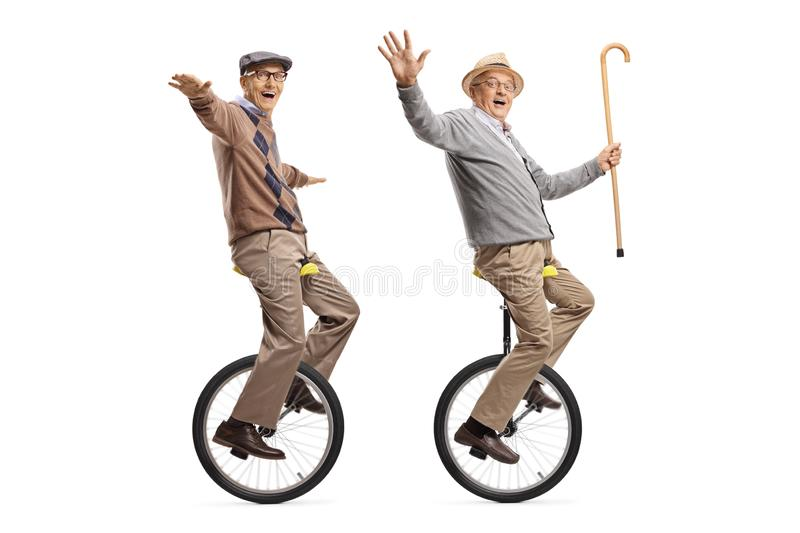 Two cheerful senior men riding unicycles and looking at the camera royalty free stock photos