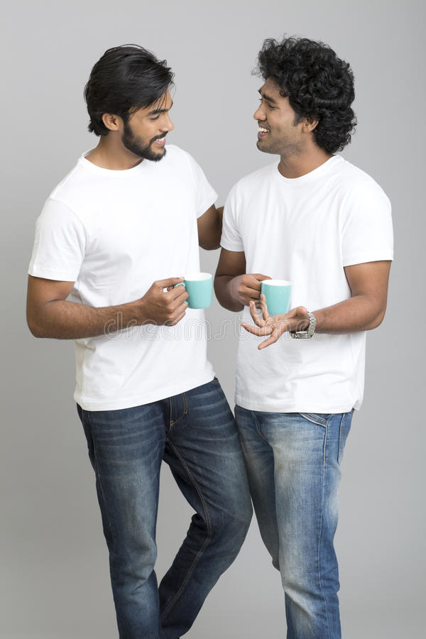 Two cheerful smart young male standing and chatting with cup of coffee royalty free stock photo